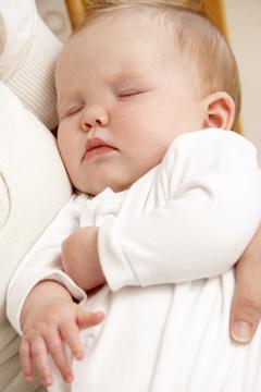Bébé dort dans les bras de maman